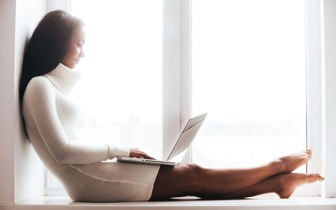 Young African woman in white sweater on laptop by window indoors