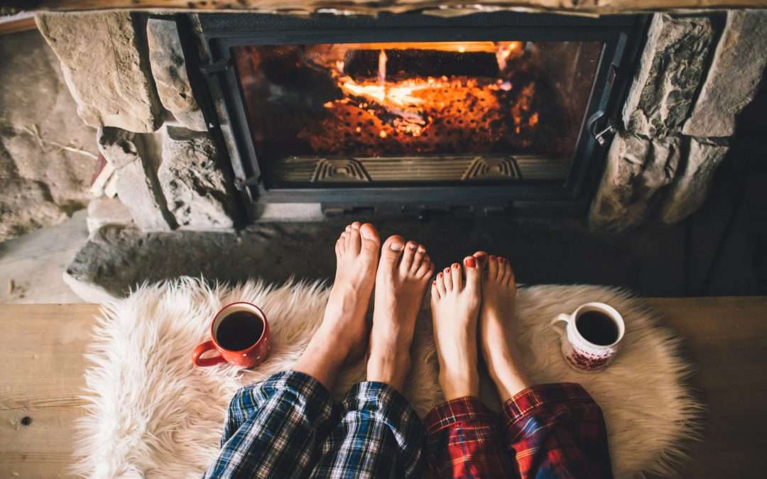 Man and woman's feet by warm fire with coffee